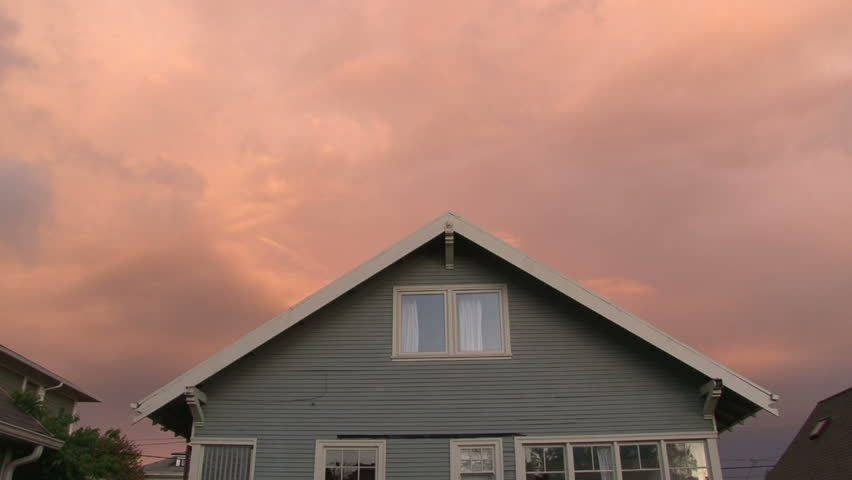 Full sunset over house with lights turning on and off as night falls.