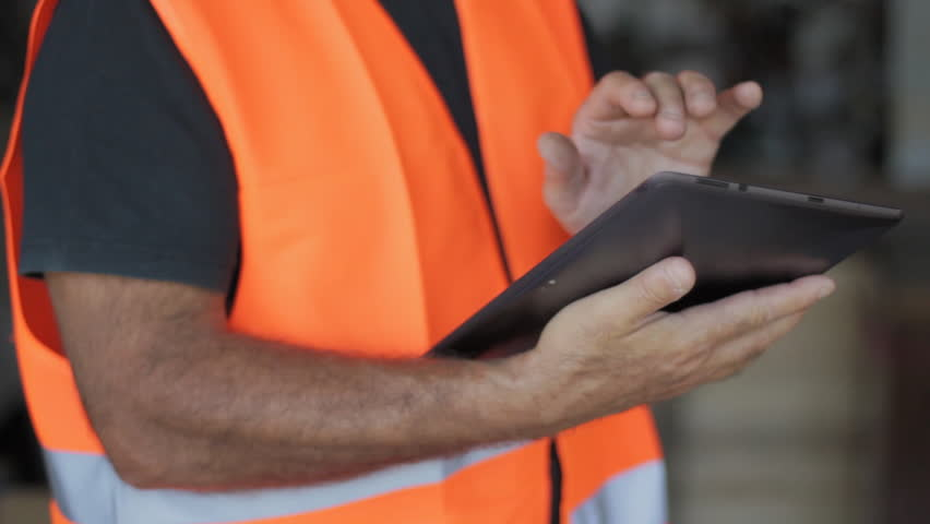 Warehouseman with protective vest and tablet in warehouse control orders