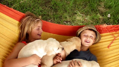 Boy and girl with puppies lying in hammock in slow motion