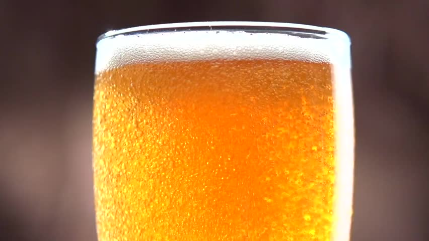 Beer is pouring into the glass. Bubbles. Slow motion video footage 1080p