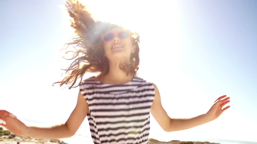 Jumping girl with blue sky and sun flare in slow motion