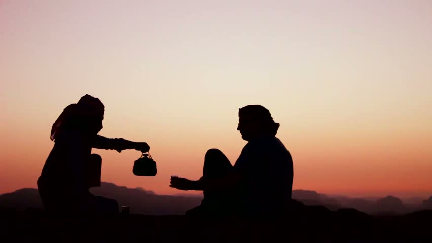 WADI RUM, JORDAN CIRCA 2013 - A Bedouin man pours tea and toasts a Western tourist in a silhouette shot.