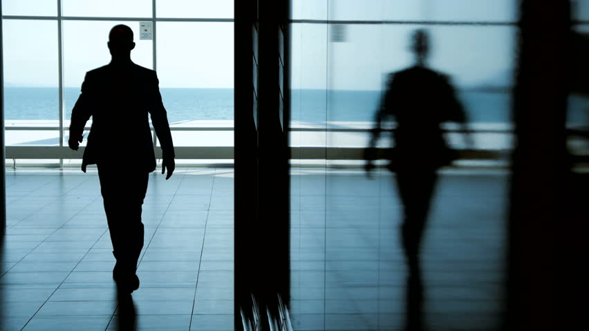 man walking in modern building. silhouette of male. person people. glass window. shadow and light. background