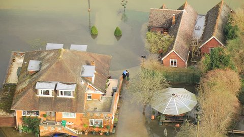 Residential flooding wide area, England, UK - Aerial view large residential properties affected by server river flooding Thames Valley, Surrey, England, UK