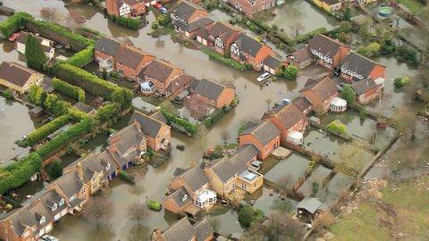 Environmental damage by flooding, Surrey, UK - Aerial close up view environmental damage by floodwater around dwellings from rivers bursting banks, England, UK