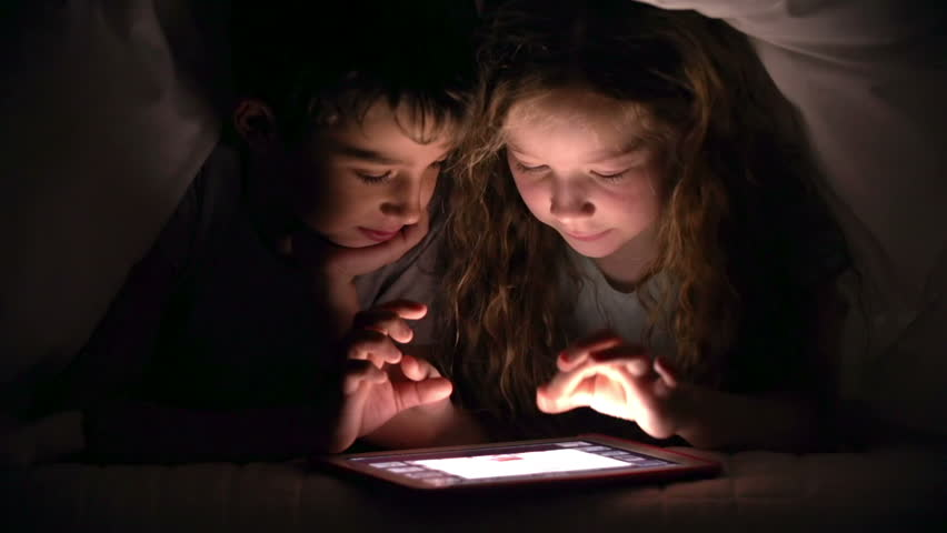 Siblings examining pics on tab under blanket