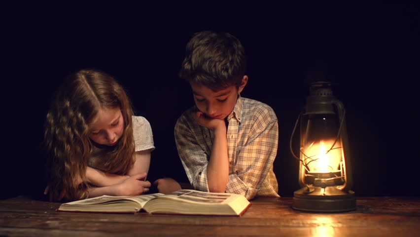 Handheld shot of children staring at the book page at night