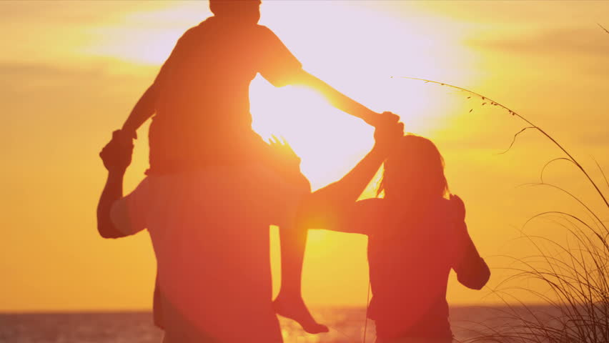 Ethnic Family Vacation Sunset Beach - Young boy on fathers shoulders as family in silhouette stand on beach watching sunset slow motion shot on RED EPIC | Shutterstock HD Video #6331661