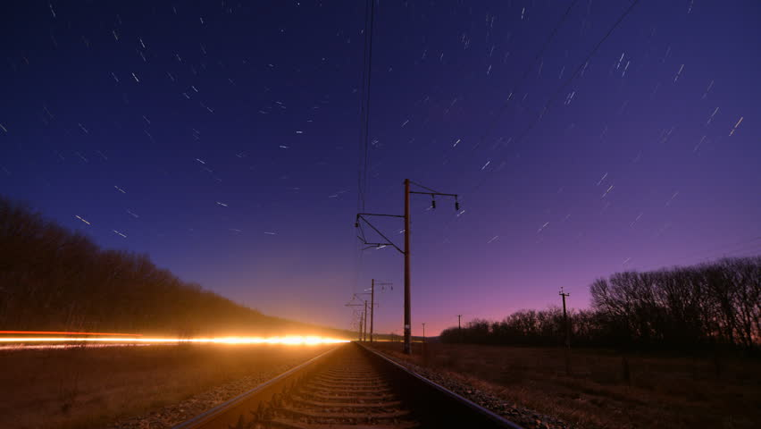 Night rails -green light train way with motion stars, star trails skies timelapse