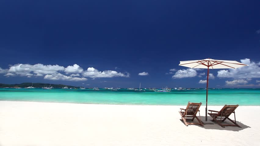 Sun umbrellas and beach chairs on coastline with white sand. Boracay, Philippines