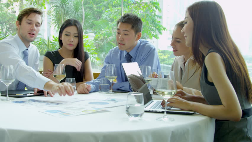 Caucasian Asian Chinese group financial investors collaborating future business plans together lunch meeting using laptop spreadsheets shot on RED EPIC | Shutterstock HD Video #6371393