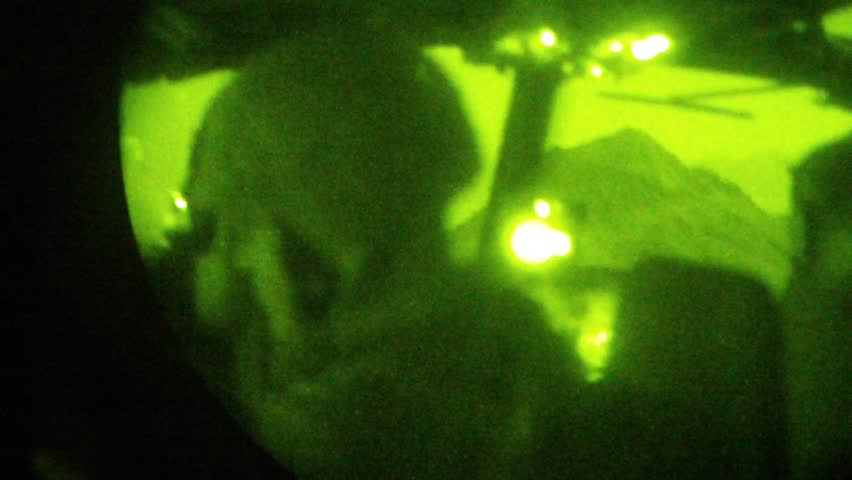 Night Vision: point of view of helicopter cockpit and mountain outside windshield