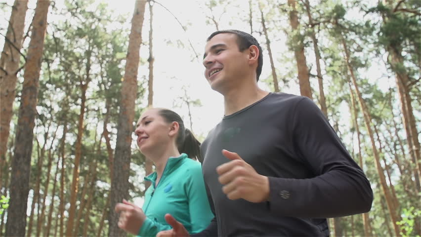 Tracking slow-motion of girl and guy communicating and smiling during morning jog