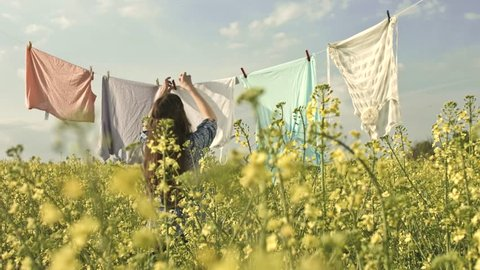 Ecology Living Concept Pretty Girl Hanging Clothes on Summer Field
