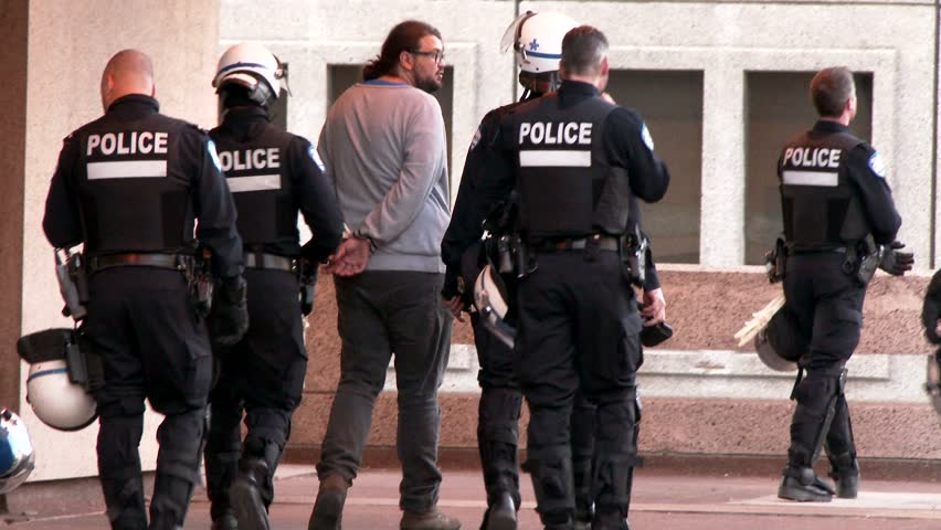 Protesters arrested by riot police. Two protesters are handcuffed with plastic restrain devices and carried away by police officer in riot uniform.