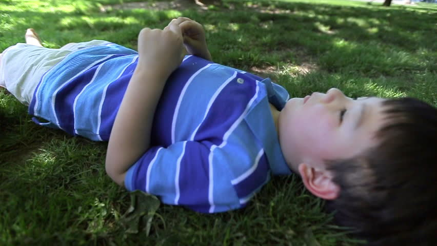 Six Year Old Laying Down In The Grass, Under A Tree, Looks Up Peacefully