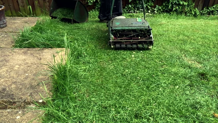 A manual cylinder mower mowing a lawn in super slow motion.