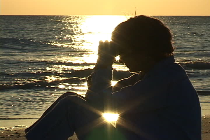 Mature woman sits on the beach praying with hands folded against head. Sunlight sparkles on the water in the background. Shot on miniDV from a tripod.