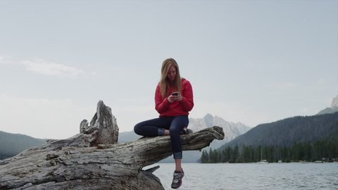 Medium shot of young woman using cell phone on log at lake / Redfish Lake, Idaho, United States