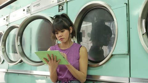 A Young Woman sits using her Digital Tablet whilst waiting for her laundry