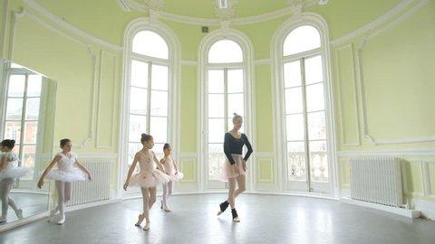 Female Ballet Dancer leads three young Ballerinas, sweeping across the Studio floor