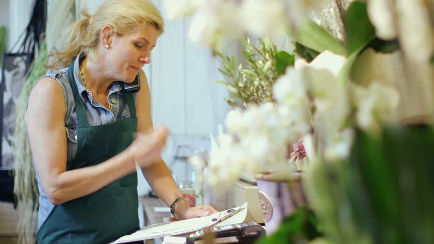 A Florist stands in her shop speaking on the phone, writing notes and inspecting the shop's supplies