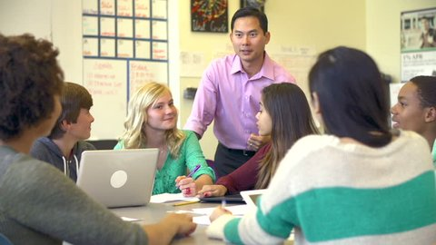 High School Students Collaborating On Project In Classroom