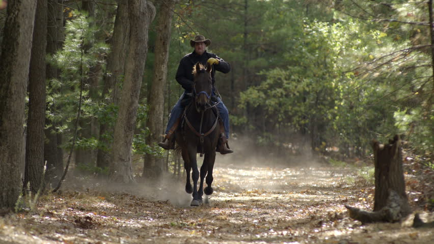 Wide shot of an older man riding a horse towards the camera in slow motion