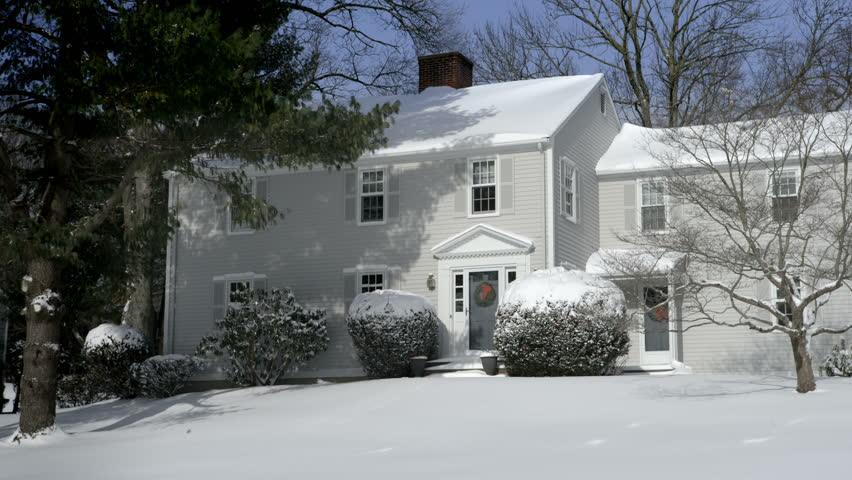 A suburban house is covered in snow after a storm. The front lawn is all white and things are calm