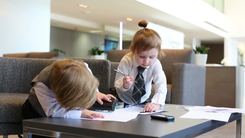 Boy plays with stapler and girl draws with ruler in business center