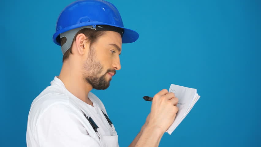 Builder or workman in a hardhat referring to a page of notes in his hands as he stands facing a blue wall with copyspace | Shutterstock HD Video #6487175