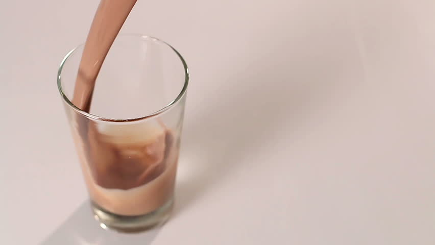 Bottle pouring milk chocolate into a glass