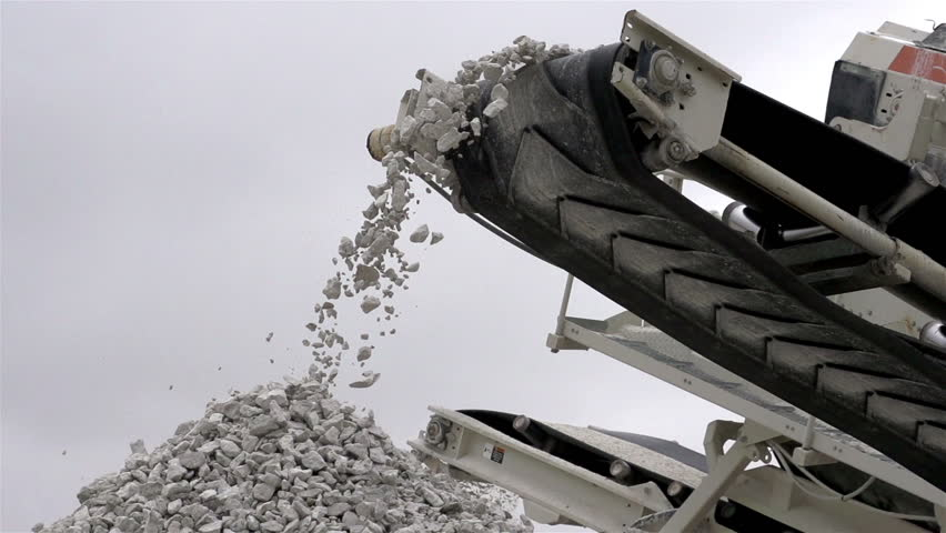 Splinters belt is rolling and dropping off gravels on the heap of rocks