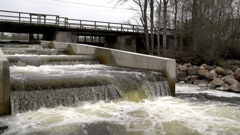A fish ladder with rushing water found underneath a bridge