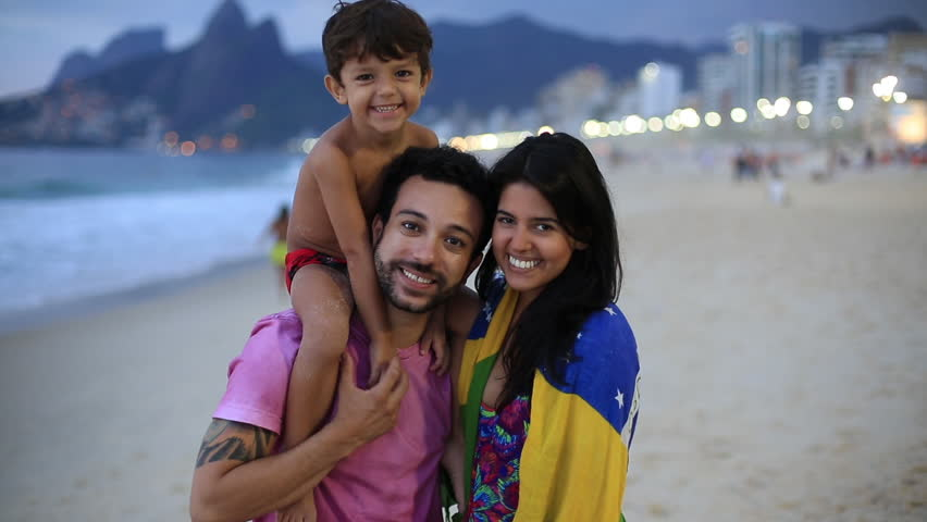 A young family stands on the beach at night and smiles into the camera | Shutterstock HD Video #6513545