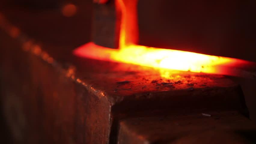 Blacksmith forging red hot iron on anvil, extreme closeup