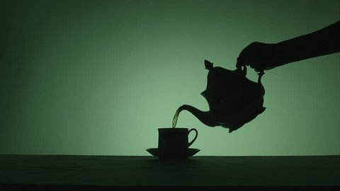 Silhouette of a traditional English teapot pouring tea into china tea cup on green background. Shot mid range and side on.