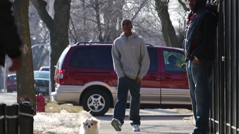 Chicago, Circa 2013: A young African/American man walks with swagger down city street in Chicago, Circa 2013. Street corner activity in a high crime area