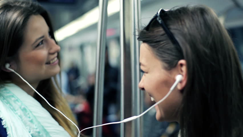 Happy girlfriends listen to music and singing while ride metro train