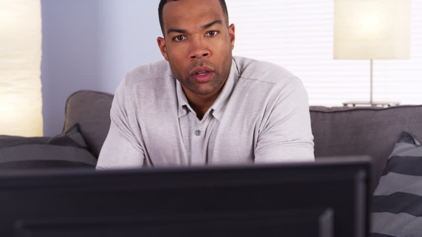 African man watching the game on TV