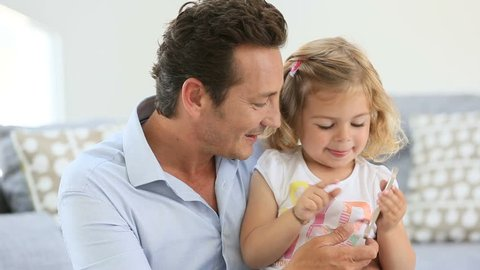 Man with cheerful little girl playing with smartphone