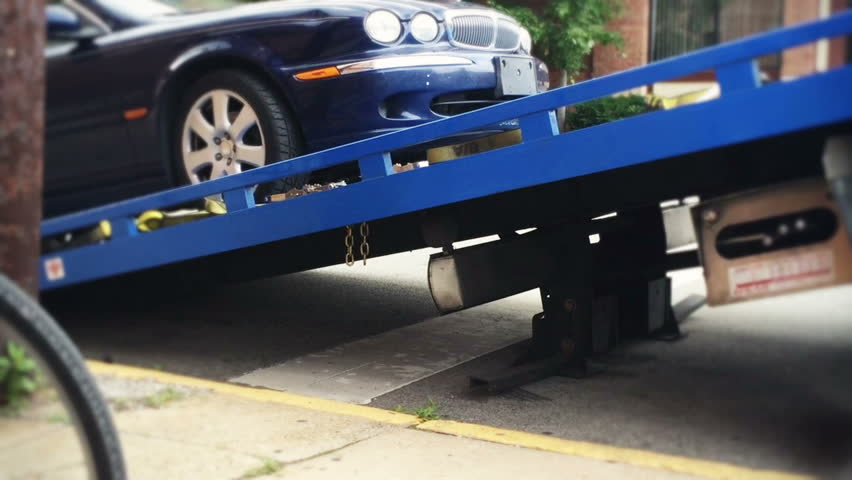 A car gets loaded onto the bed of a towing truck.