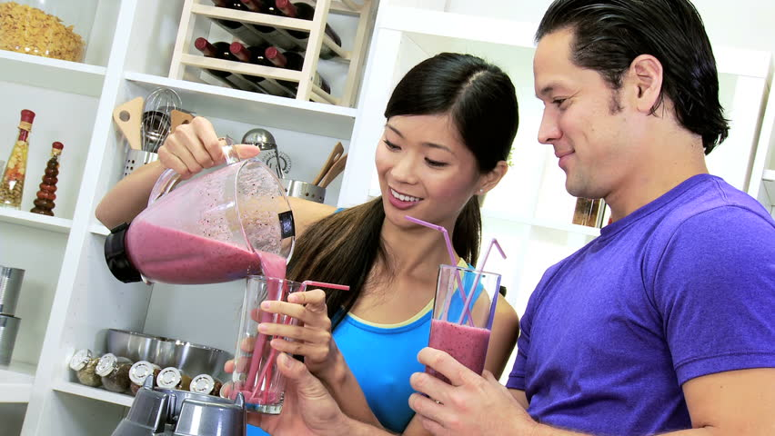 Young heterosexual ethnic couple domestic kitchen pouring delicious healthy smoothie made fresh organic fruit electric blender | Shutterstock HD Video #6665825
