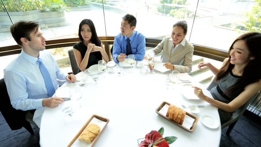 Male female Asian Chinese Caucasian banking executives toast sealing future business together lunch meeting city restaurant | Shutterstock HD Video #6677735