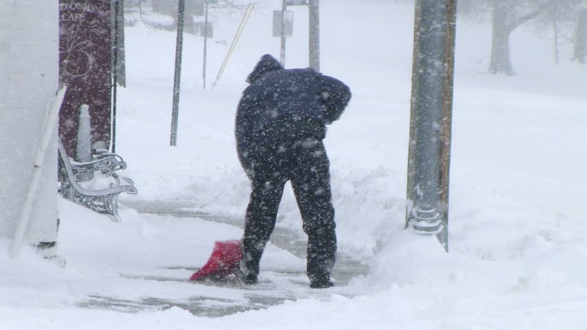 Man shoveling snow to clear sidewalk during late winter blizzard.