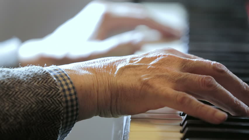 aged hands playing classical music at the piano: musician, arrangement, notes,