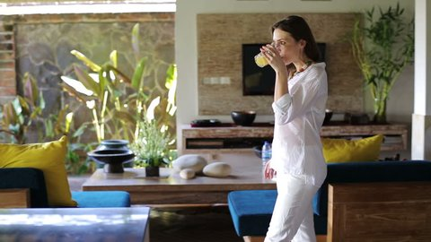 Beautiful woman drink juice and walking in luxury home