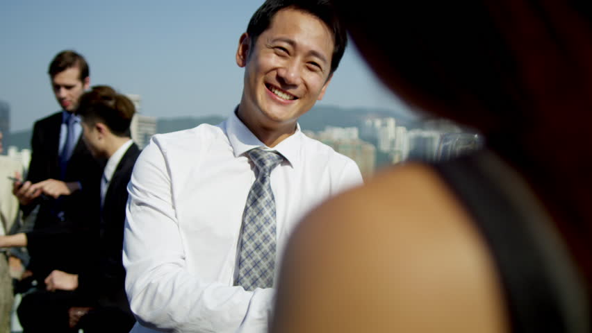 Smart young male female Asian Chinese business managers foreground multi ethnic business team tablet together outdoors rooftop downtown shot on RED EPIC | Shutterstock HD Video #6724165