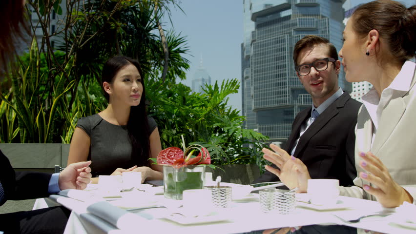 Caucasian businessman discussing future plans male female prospective Asian Chinese business partners using wireless technology modern city rooftop restaurant shot on RED EPIC | Shutterstock HD Video #6725065