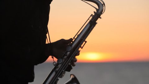 The silhouette of a musician masterly playing saxophone on the seacoast at amazing sunset